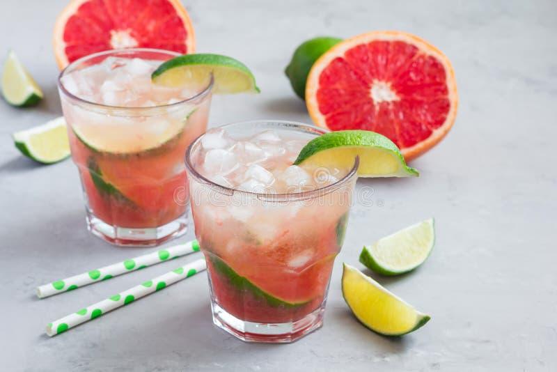 Kall rosa coctail med den nya grapefrukten, limefrukt, kopieringsutrymme fotografering för bildbyråer