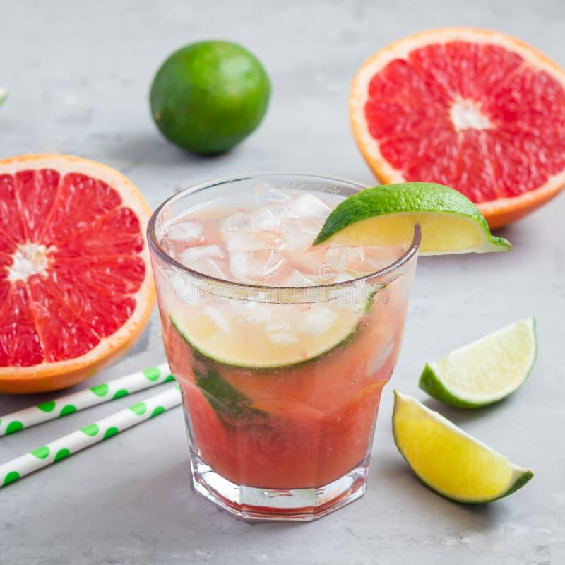 Kall rosa coctail med nya grapefrukt-, limefrukt- och iskuber på konkret bakgrund, paloma, fyrkant royaltyfri foto