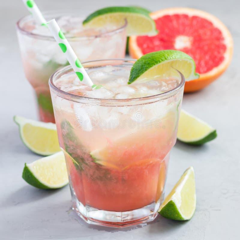 Kall rosa coctail med nya grapefrukt-, limefrukt- och iskuber på konkret bakgrund, paloma, fyrkant arkivfoton