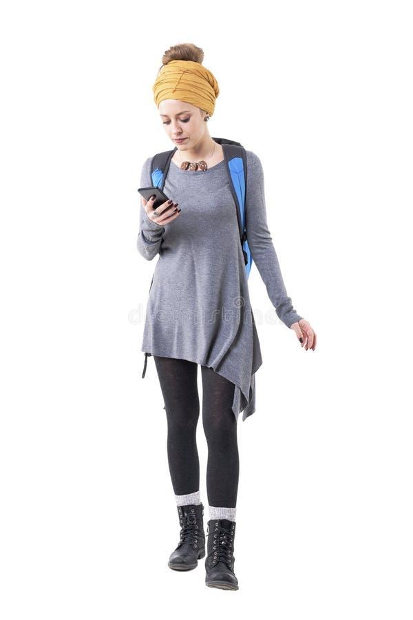 Kall stilfull modern hipsterkvinna med ryggsäcken som söker för ställen på mobiltelefonapplikation arkivbild