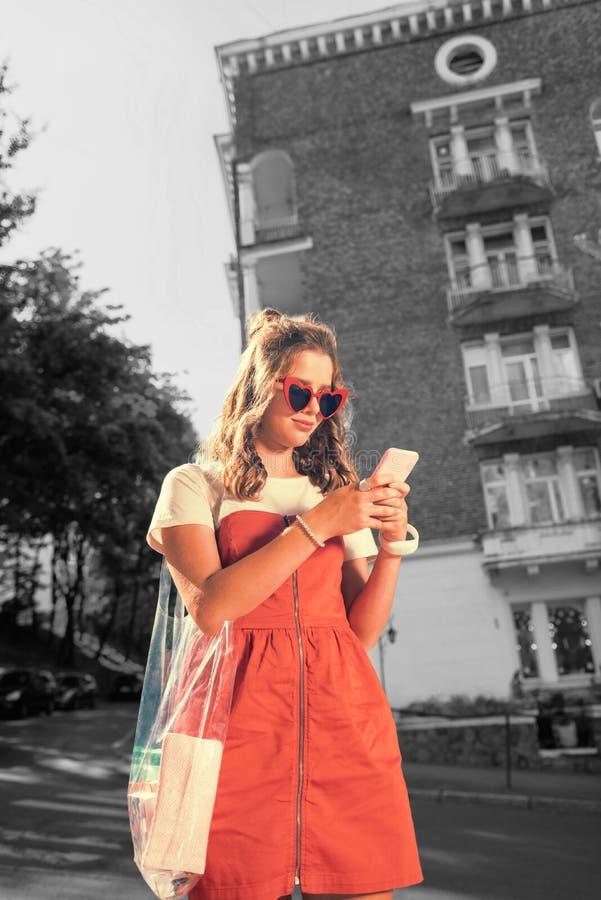 Kall stilfull student som bär den röda klänningen som rymmer rosa smartphoneläsningmeddelanden royaltyfria foton