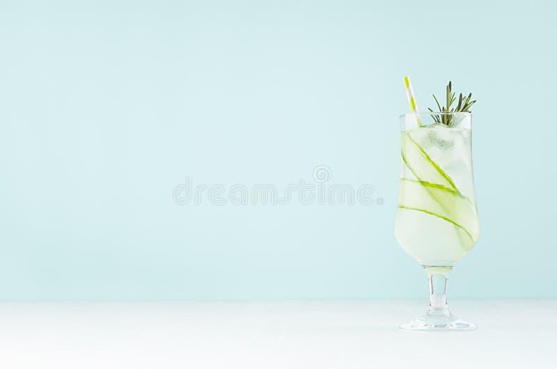 Kall sur lerig hemlagad coctail med iskuber, gurkaskiva, rosmarin, sugrör i mjuk ljus inre för mintkaramellfärgstång royaltyfri fotografi