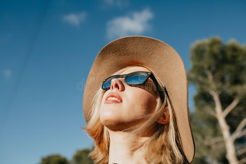 Kall ung flickastående med solglasögon och hatten utomhus i natur royaltyfria bilder