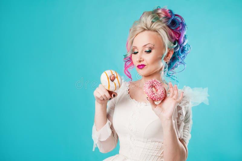 Kall ung kvinna med kulört hår Håll två söta donuts som är roliga royaltyfri foto