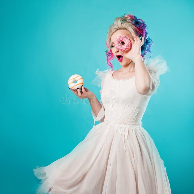 Kall ung kvinna med kulört hår Håll två söta donuts som är roliga arkivbilder