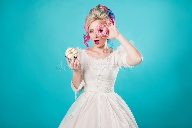 Kall ung kvinna med kulört hår Håll två söta donuts som är roliga arkivfoto