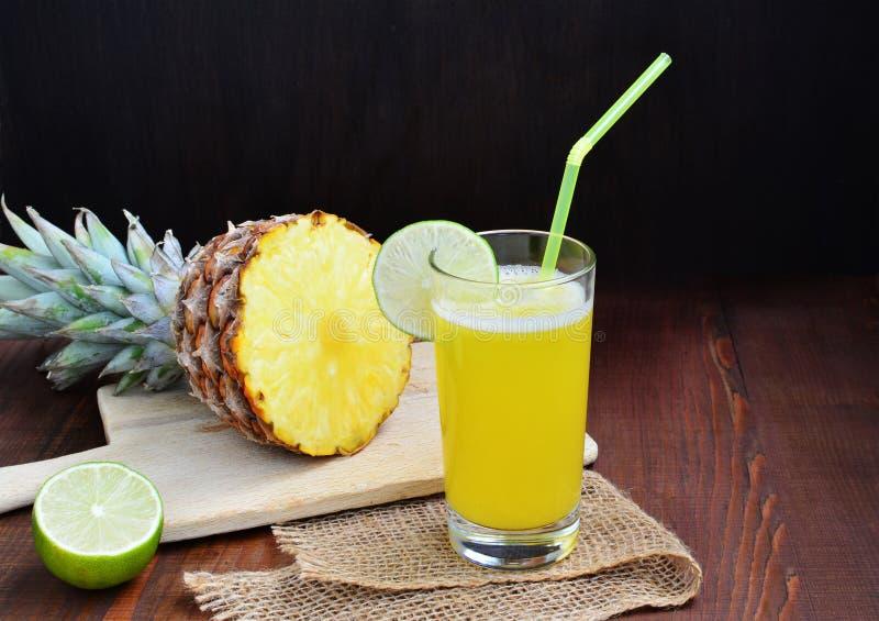 Kall uppfriskande ananascoctaildrink med limefrukt i exponeringsglas royaltyfri fotografi