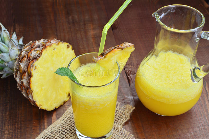 Kall uppfriskande ananasmocktaildrink i exponeringsglas och kanna royaltyfria foton