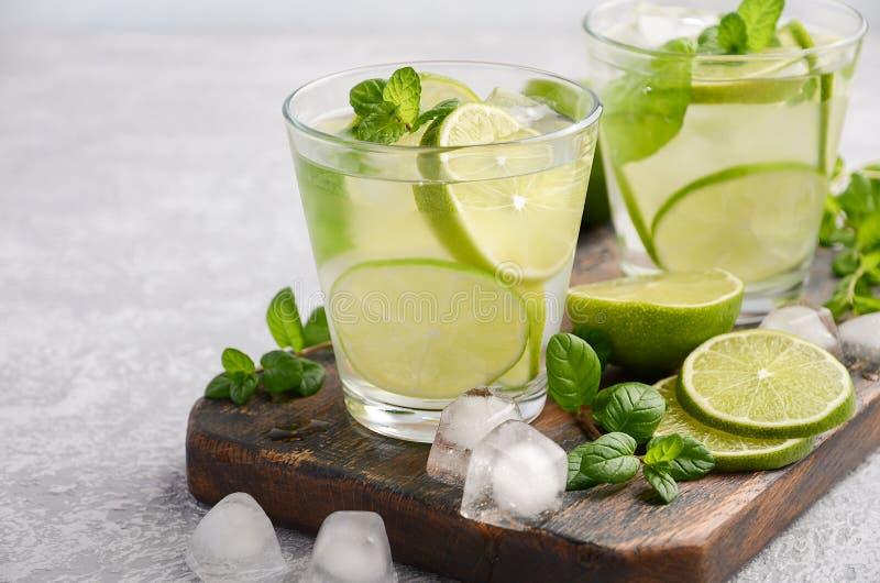 Kall uppfriskande sommardrink med limefrukt och mintkaramellen i ett exponeringsglas på en grå betong- eller stenbakgrund arkivbild