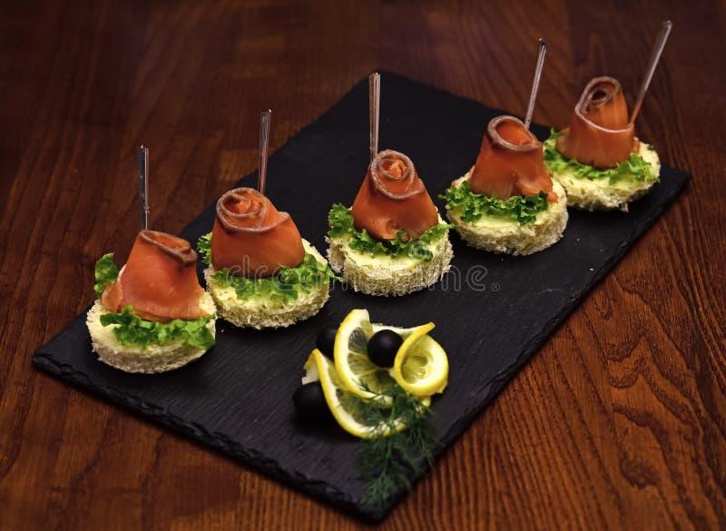 Kalla aptitretare, canape med den röda fisken, träbakgrund Canape med salladsidor, den röda fisken, citronen och dill läckert arkivfoton