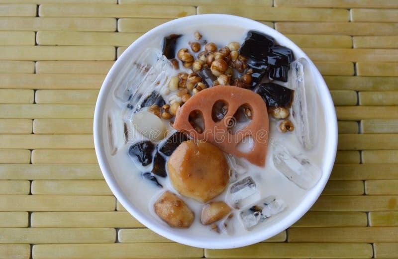 Kalla blandade bönor mjölkar och täcker med sirap in den kinesiska efterrätten på koppen arkivbilder