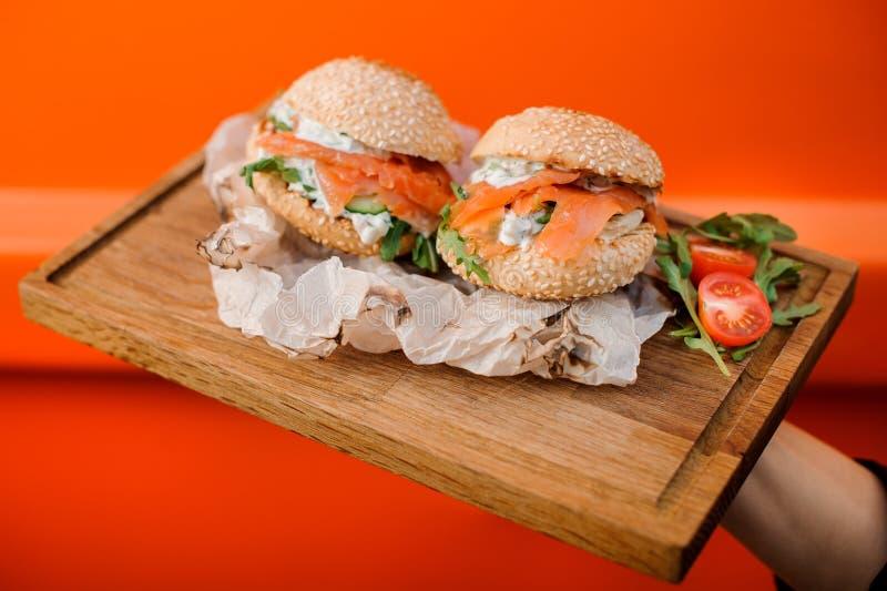 Kalla hamburgare med laxen, sås, gurkan, tomaten och arugula tjänade som i träplattan royaltyfri bild