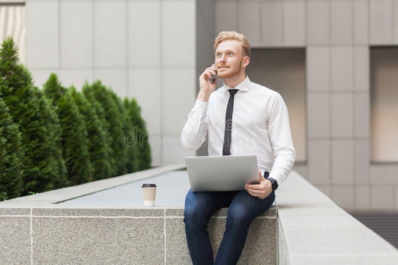 Kalla i smart telefon Affärs- och framgångbegrepp Ung vuxen ljust rödbrun man arkivbild