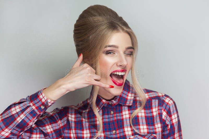 Kalla mig! rolig härlig blond flicka i den rosa rutiga skjortan, Co arkivbild