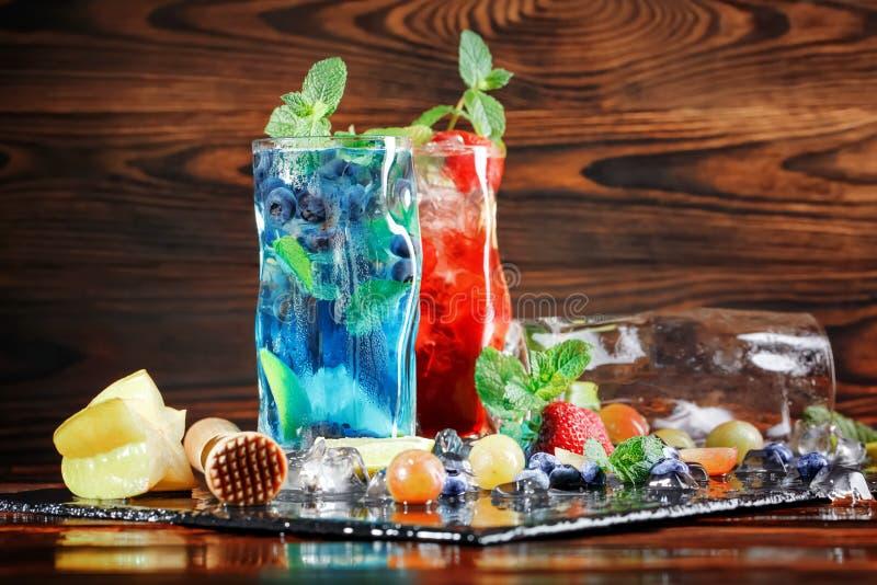 Kalla mojitos med jordgubbar och blåbär Exponeringsglas av mojito och frukter på en träbakgrund Sommarcoctailar kopiera avstånd royaltyfri fotografi