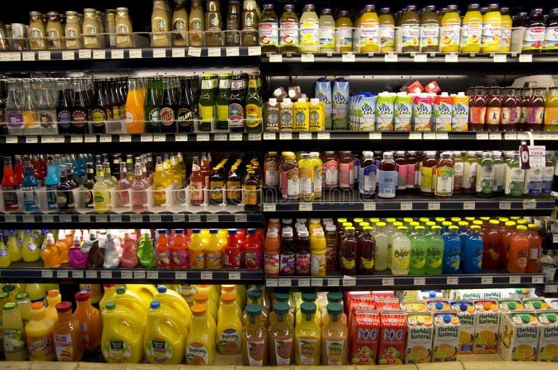 Kalla sunda drinkar på supermarkethyllor arkivfoton