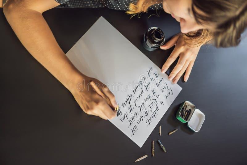 Kalligrafh?nder skriver uttryck p? vitbok Bibeluttryck om f?r?lskelse som inskriver dekorativa dekorerade bokst?ver royaltyfri foto