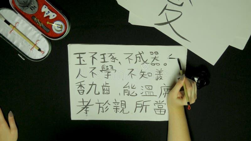 Kalligrafi för kines för handstil för hand för kvinna` s Kvinnlig hand som rymmer kinesiska tecken för en handstilborste royaltyfri bild