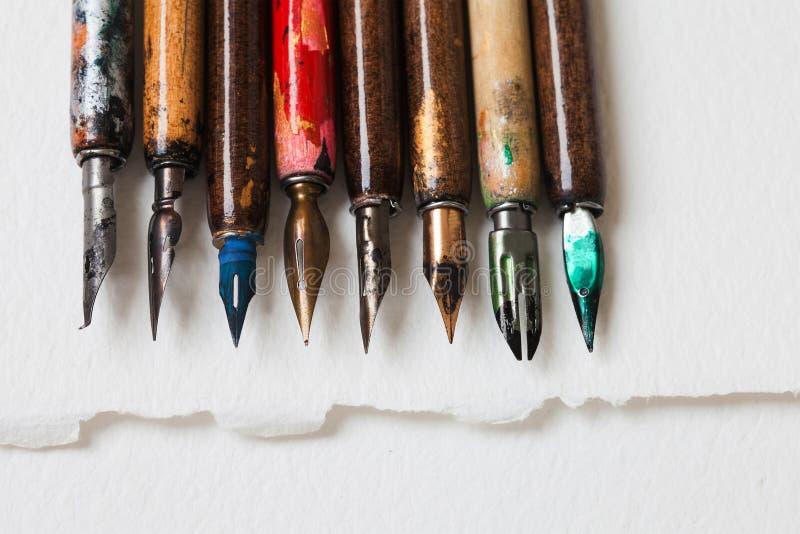 Kalligrafische toebehoren, retro inzameling van de stijlvulpen Oude kleurrijke kunstenaarspennen, geweven Witboek royalty-vrije stock fotografie