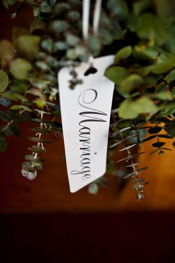 Kalligraphieaufkleber-Sprechenheirat hängt an einem Korb von eleganten Anlagen stockfotos