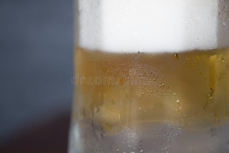 Kallt öl i ett exponeringsglas med vattendroppar arkivbild