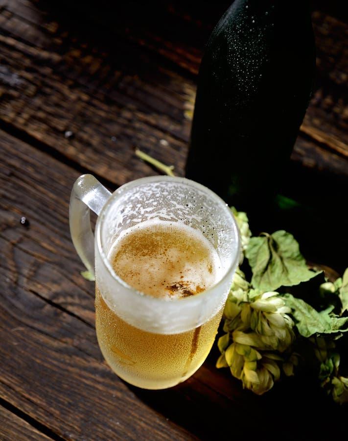 Kallt öl i exponeringsglas, flaska och flygturer på en mörk träbakgrund royaltyfria foton