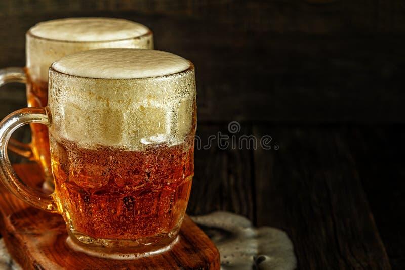 Kallt öl i exponeringsglas med chiper på en mörk bakgrund royaltyfri bild