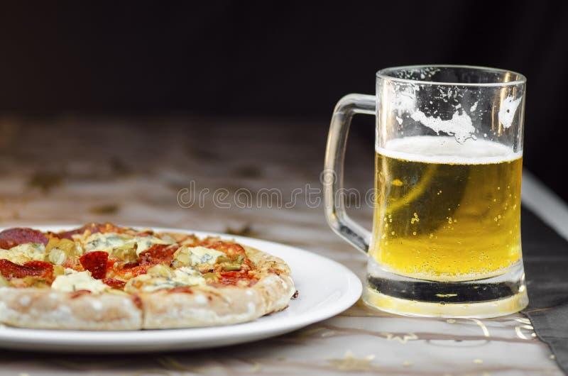 Kallt öl rånar och peperonipizza royaltyfri foto