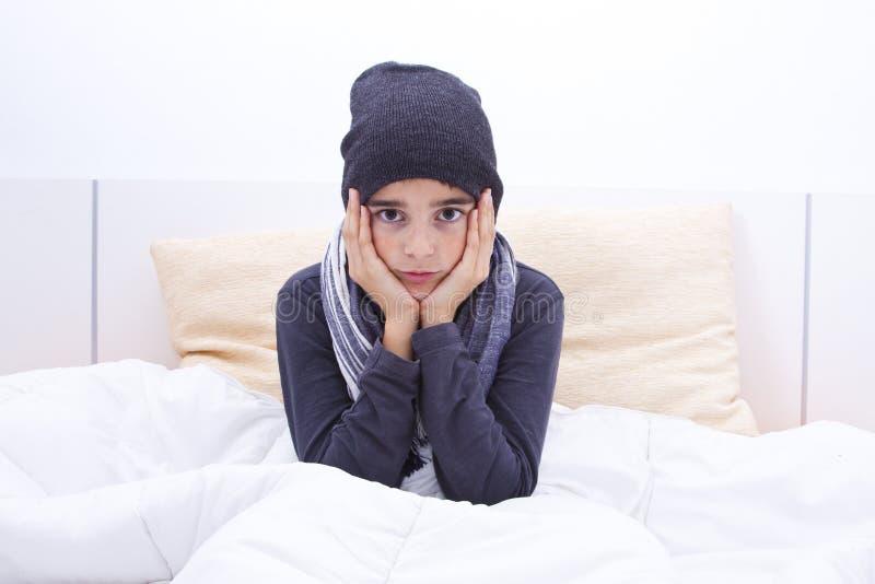 Kallt barn i säng royaltyfri bild