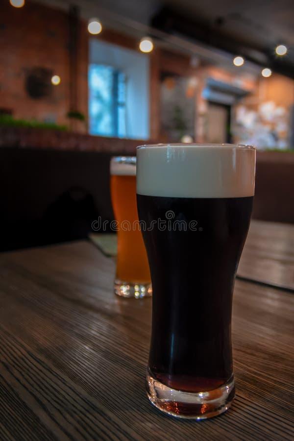 Kallt exponeringsglas av mörkt kraft ölanseende på trätabellen på en stång Skum på det kraftiga ölet Bar i bakgrunden royaltyfri bild