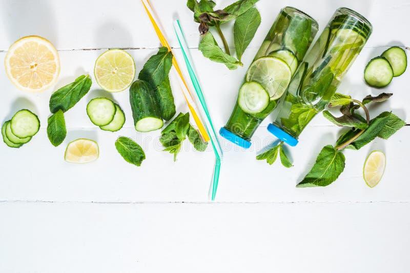 Kallt och förnyande ingett detoxvatten med limefrukt, mintkaramellen och gurkan i en flaska på vit wood bakgrund Copyspace och royaltyfri fotografi