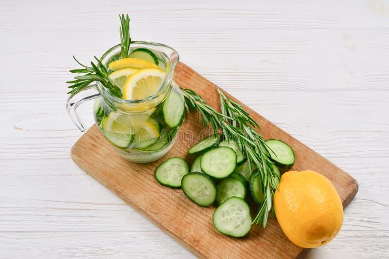 Kallt och uppfriskande detoxvatten med citronen, gurkan, rosmarin och is i den glass kruset arkivbild