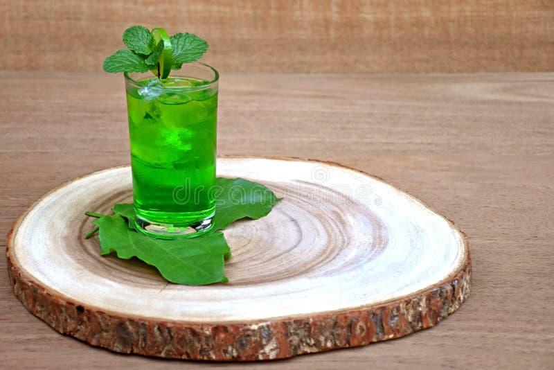Kallt och uppfriskande limefrukt- och mintkaramellgräsplanvatten i ett exponeringsglas på trä royaltyfri foto