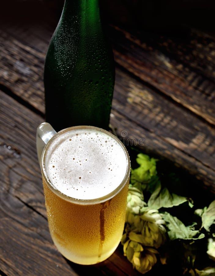 Kallt skummigt öl i en glasflaska och flygturer på en mörk träbakgrund royaltyfri fotografi