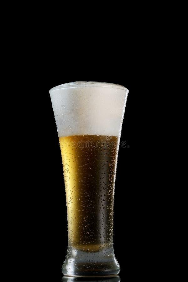 Kallt skummigt öl i ett exponeringsglas av den original- formen på en svart bakgrund arkivfoton