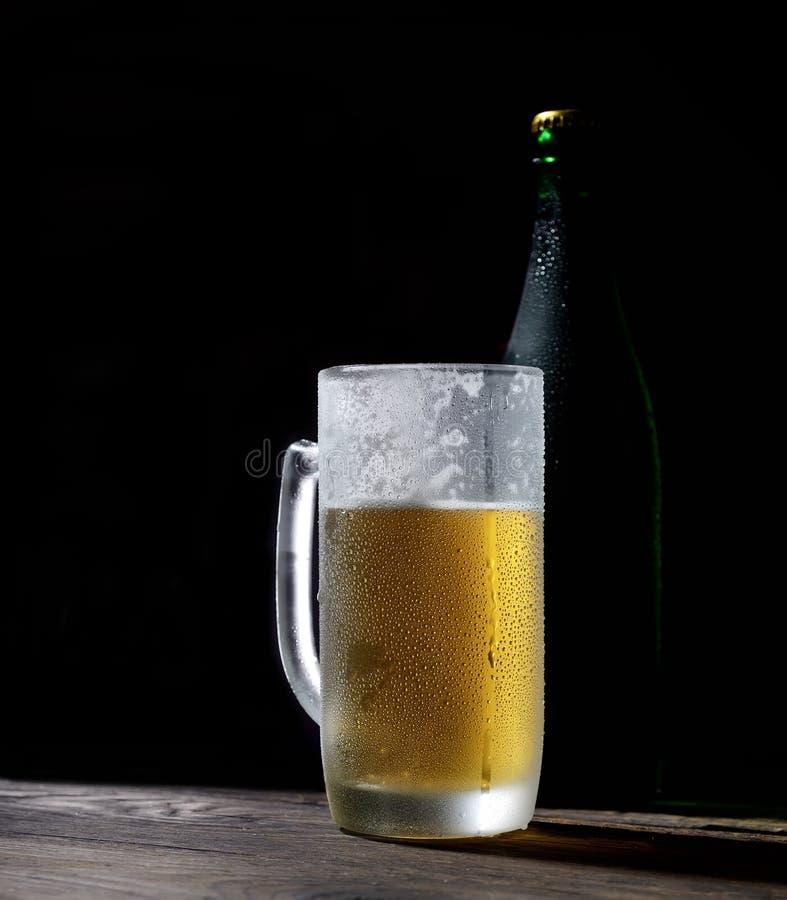 Kallt skummigt öl i ett exponeringsglas och en flaska på träbräden på en svart bakgrund royaltyfria bilder