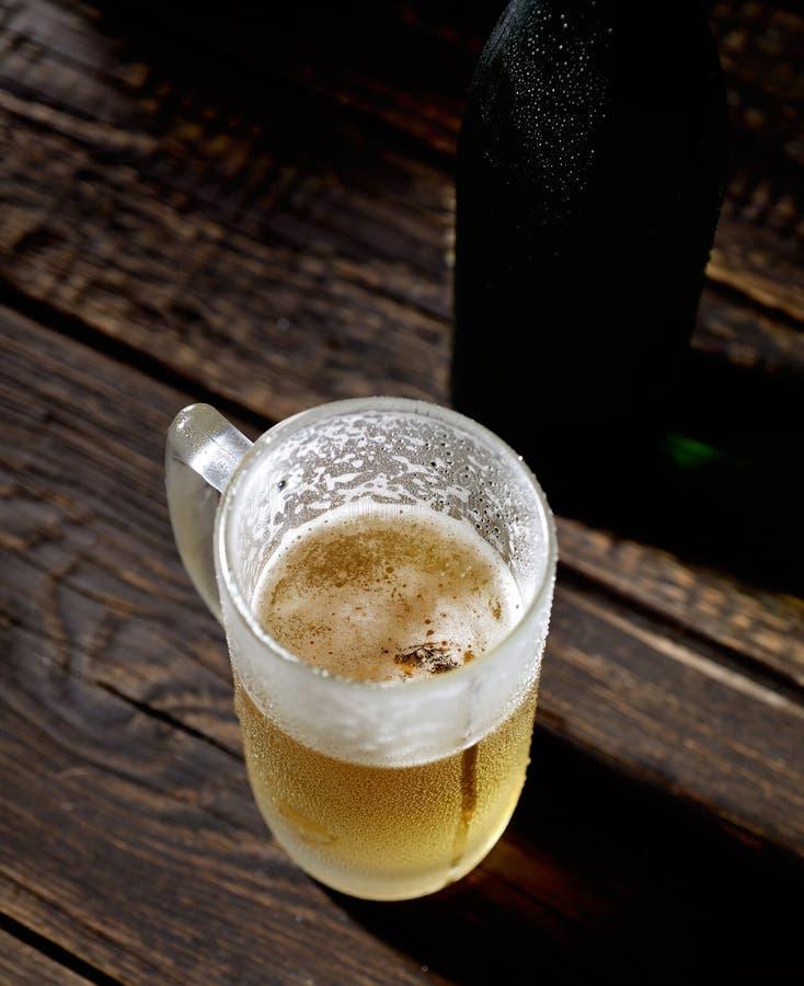 Kallt skummigt öl i exponeringsglas på en träbakgrund arkivfoto