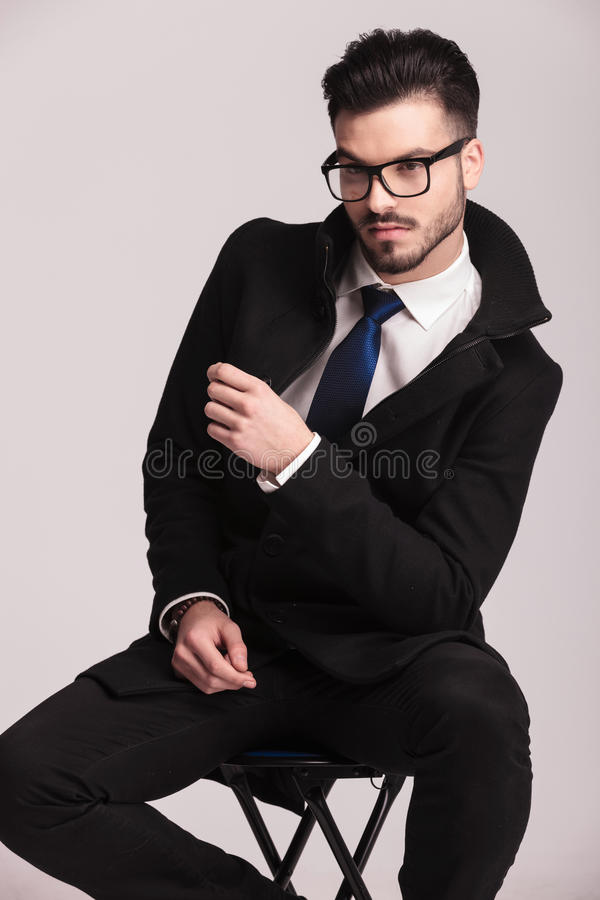 Kallt ungt sammanträde för affärsman på en stol arkivbild
