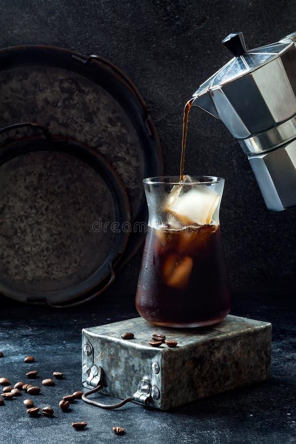 Kallt uppfriskande med is kaffe i ett högväxt exponeringsglas och kaffebönor på mörk bakgrund Hällande kaffe från mokakrukan in i arkivbild