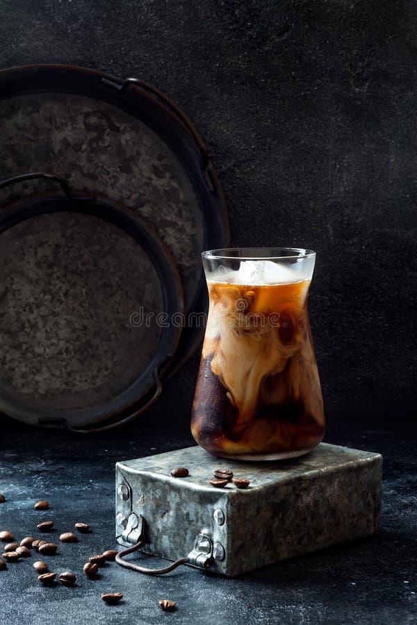 Kallt uppfriskande med is kaffe med kräm i ett högväxt exponeringsglas och kaffebönor på mörk bakgrund royaltyfria foton
