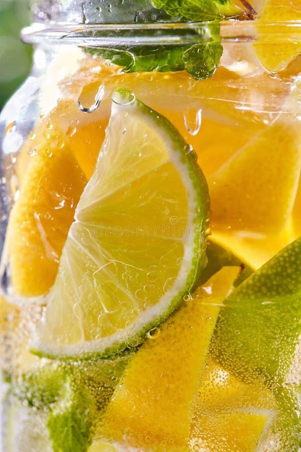 Kallt uppfriskande vatten med limefrukt och citronen i ett exponeringsglas arkivfoto