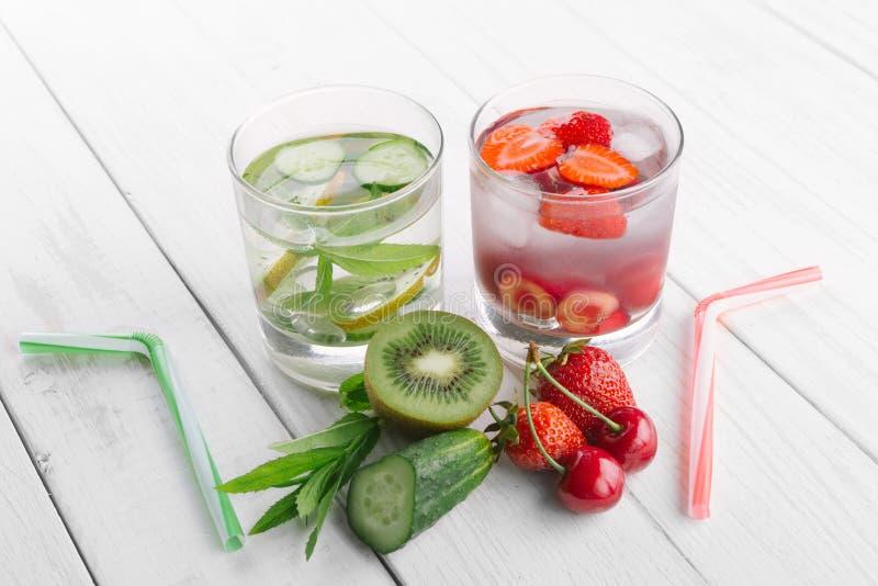 Kallt vatten i exponeringsglas, ny grön kiwi, mintkaramell och gurka, jordgubbar och körsbär Nya hemlagade vitaminer royaltyfri foto