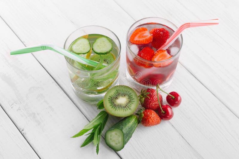 Kallt vatten i exponeringsglas, ny grön kiwi, mintkaramell och gurka, jordgubbar och körsbär Nya hemlagade vitaminer arkivfoto