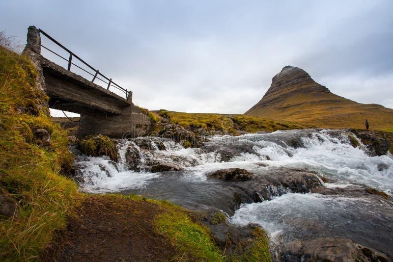 Kallt vatten i Island Vattenfall i steniga berg Nytt och G arkivfoto