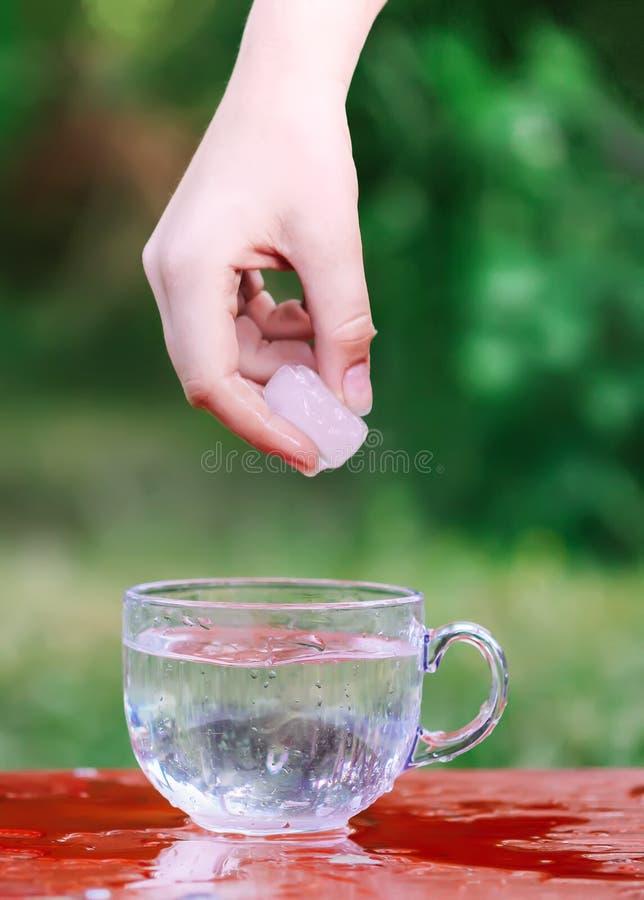 Kallt vatten och iskub i hand ovanför den genomskinliga exponeringsglaskoppen i tabelloutoorsna i sommardag royaltyfria foton