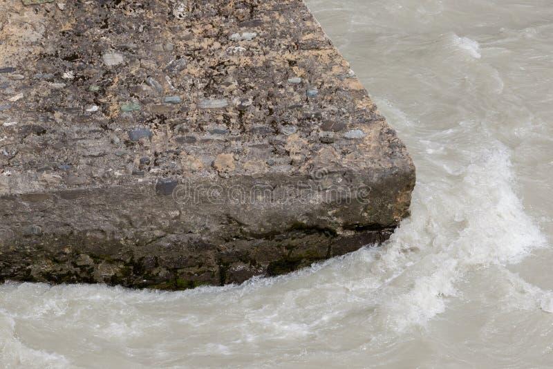 Kallt vatten som flödar runt om en konkret struktur royaltyfria foton