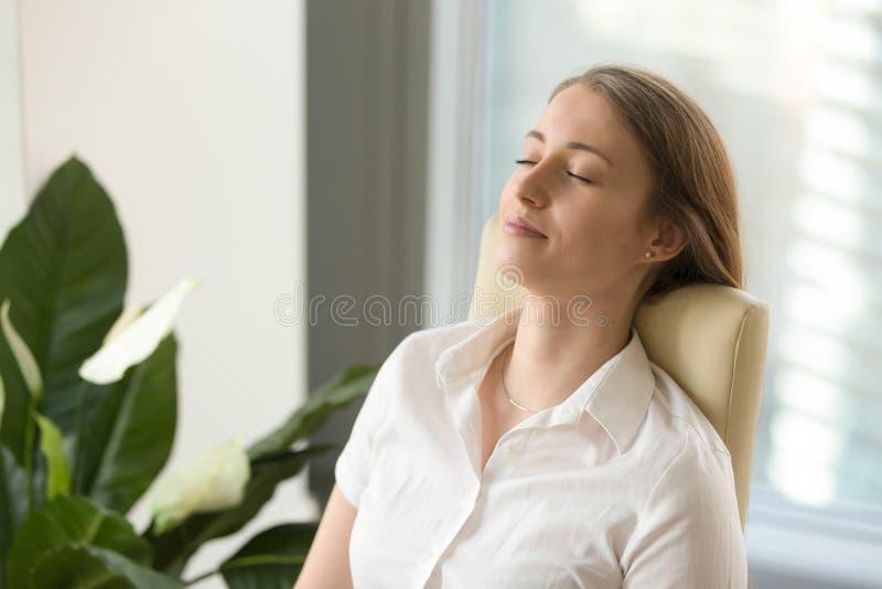 Kalm aantrekkelijk ontspannen vrouwengevoel het leunen terug op bureaucha royalty-vrije stock fotografie