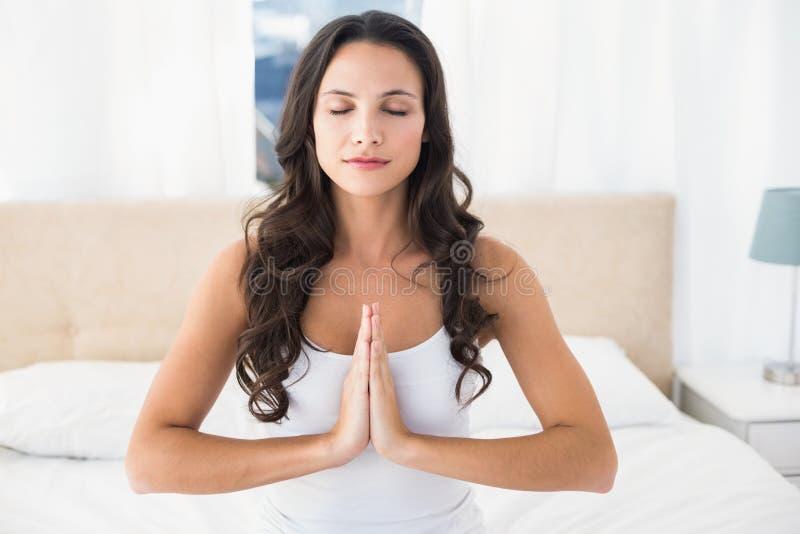 Kalm brunette die yoga op bed doen stock afbeelding