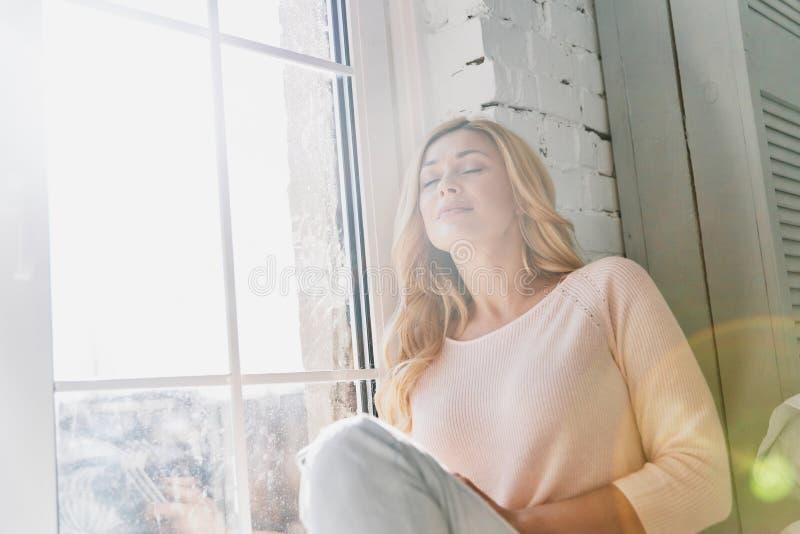 Kalm en gelukkig het voelen Aantrekkelijke jonge vrouw die ogenclos houden stock afbeelding