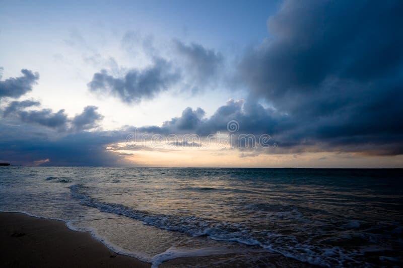 Kalm oceaan en strand op tropische zonsopgang stock afbeelding